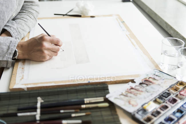Vista lateral de hembra mano con pincel y acuarelas - foto de stock
