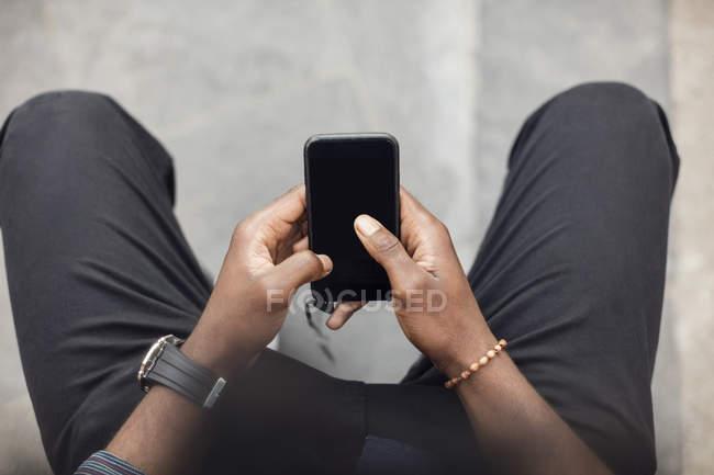 Visão de alto ângulo de mãos masculinas usando smartphone — Fotografia de Stock