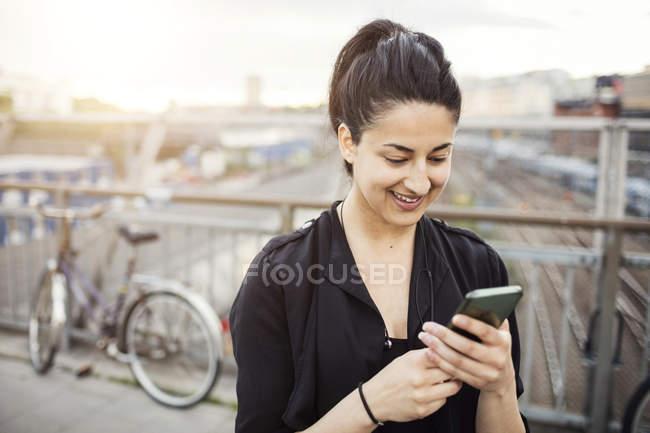 Giovane donna felice che per mezzo dello smart phone in città — Foto stock