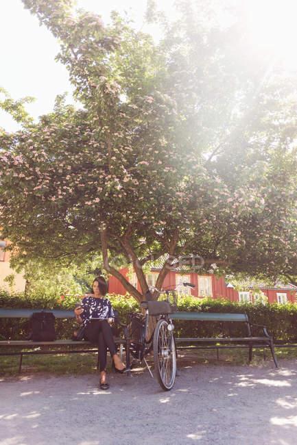 Geschäftsfrau nutzt Smartphone bei sonnigem Wetter auf Parkbank — Stockfoto