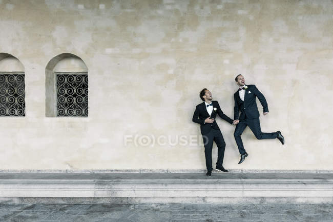 Cheerful man jumping while holding hands of gay partner on bench against wall — Fotografia de Stock