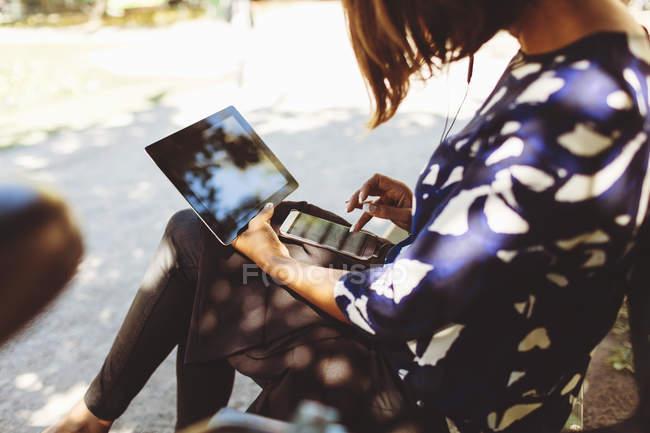 Вид збоку бізнес-леді за допомогою смарт-телефон і цифровий планшет, сидячи на лавці — стокове фото