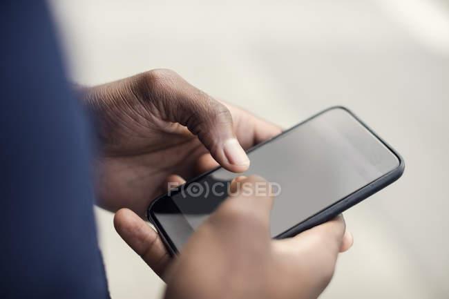 Vista de ángulo alto de las manos masculinas usando teléfono inteligente - foto de stock
