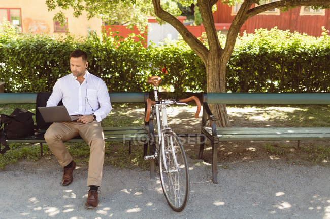 Businessman using laptop while sitting on park bench — Stock Photo