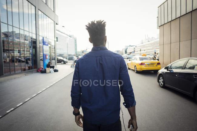 Vista trasera del hombre caminando en la ciudad - foto de stock