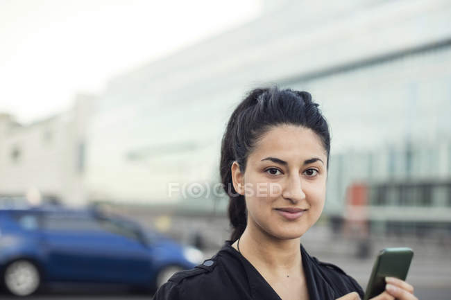 Portrait of confident woman with mobile phone against building — Stock Photo