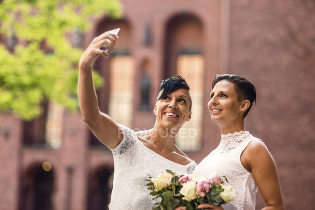 Happy lesbian couple taking selfie from mobile phone — Stock Photo