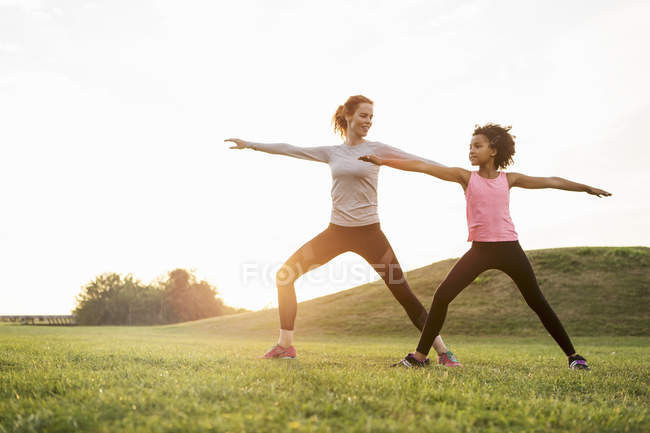 Happy mother looking at daughter exercising on grass against sky — Stock Photo