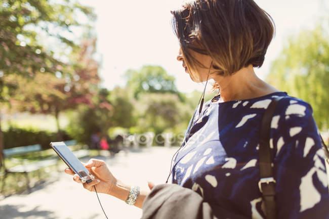 Geschäftsfrau hört bei sonnigem Tag Musik per Smartphone auf Fußweg — Stockfoto