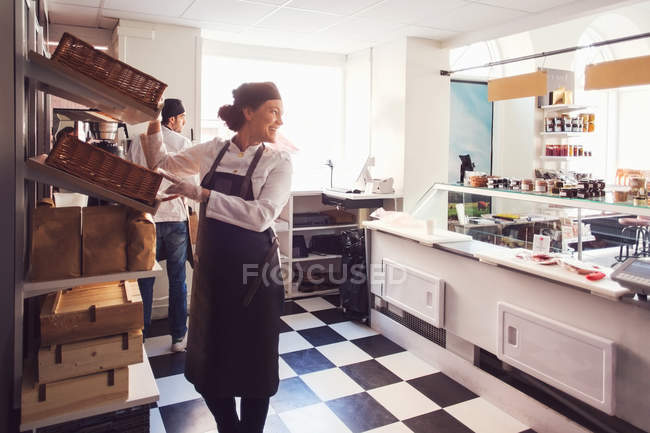 Female owner looking away while standing by shelves in brightly lit grocery store — Stock Photo