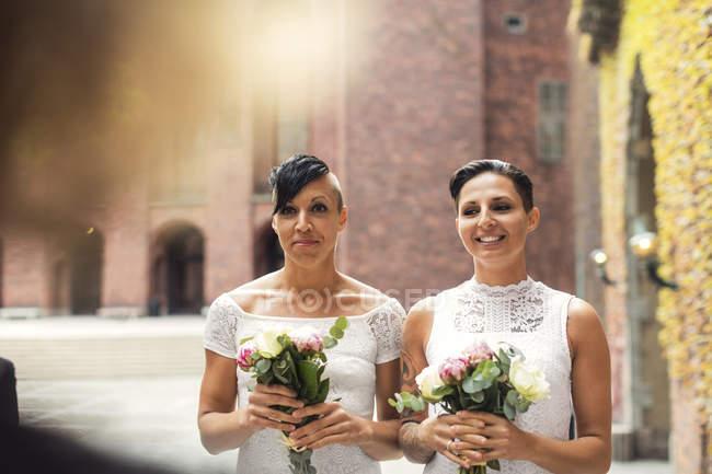 Joyeux couple lesbien tenant des bouquets de fleurs pendant la cérémonie de mariage — Photo de stock