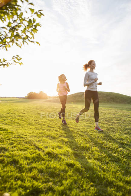 Mother and daughter running on grass at park against sky during sunset — Stock Photo