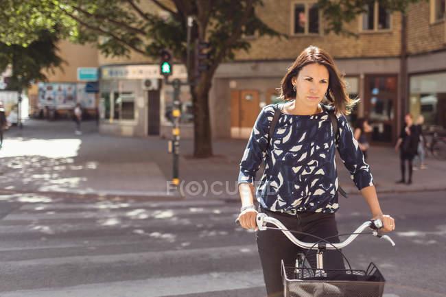 Empresária andando de bicicleta na rua da cidade — Fotografia de Stock