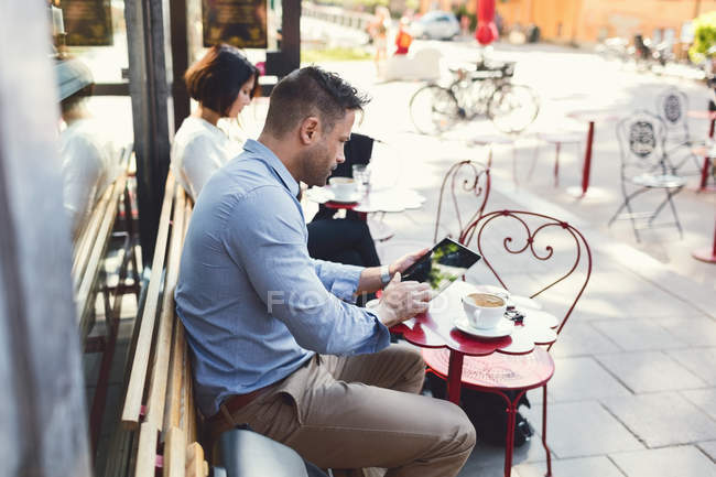 Businessman using digital tablet at sidewalk cafe — Stock Photo