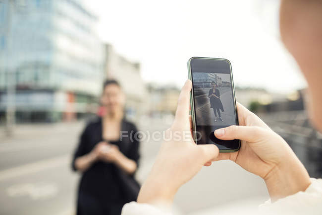 Cropped image of woman photographing friend in city — Stock Photo