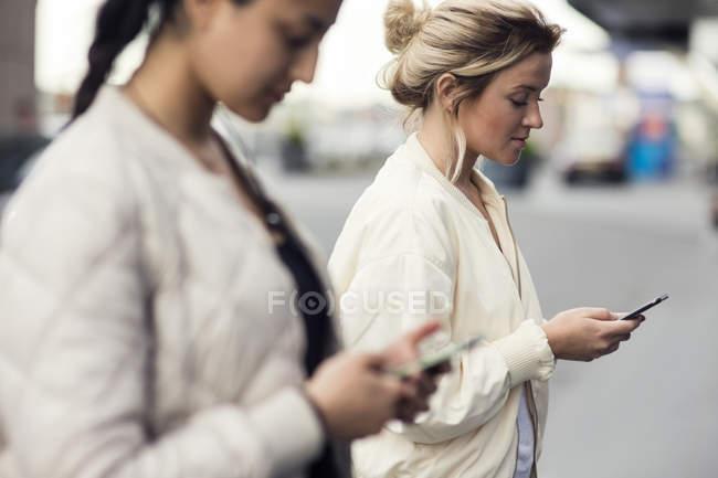 Vista lateral de mulheres jovens usando telefones móveis na cidade — Fotografia de Stock