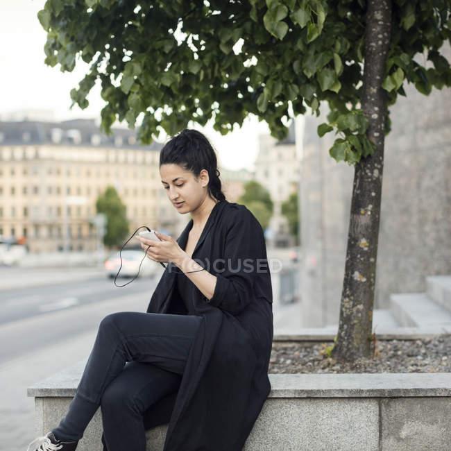 Giovane donna che usando smartphone mentre era seduto sul muro di contenimento in città — Foto stock