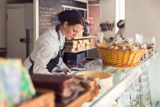 Female owner working at display cabinet in grocery store — Stock Photo