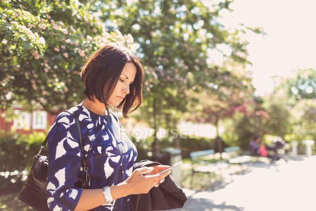 Geschäftsfrau bei sonnigem Tag mit Smartphone auf Fußweg — Stockfoto