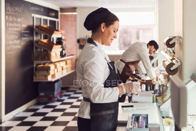 Side view of owners working at counter in grocery store — Stock Photo