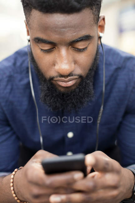 Man listening to music from mobile phone in city — Stock Photo