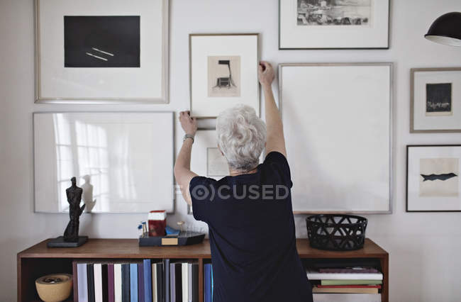Rear view of retired senior woman adjusting picture frame on wall over bookshelf at home — Stock Photo