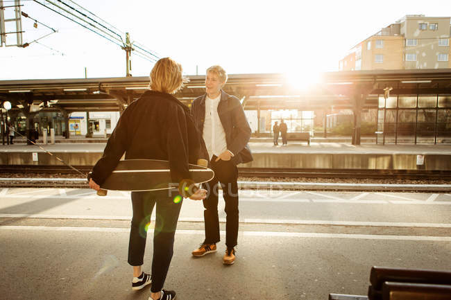 Happy teenage boy talking with teenage girl while standing on railroad station platform — Stock Photo