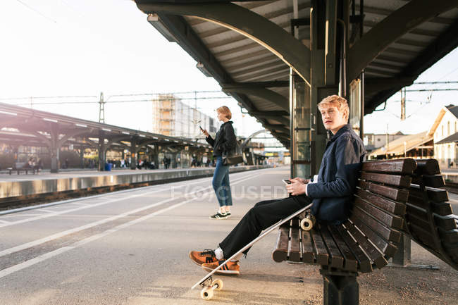 Teenage boy sitting on bench with teenage girl in background at railroad station platform — Stock Photo