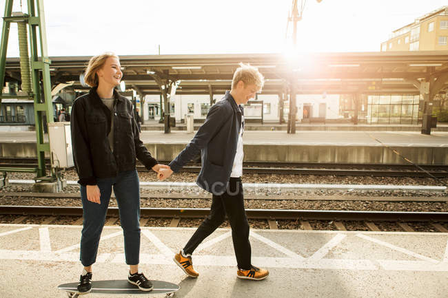 Full length of teenage boy pulling teenage girl on skateboard at railroad station platform — Stock Photo