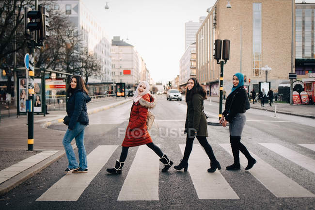 Full length of happy female friends crossing street in city — Stock Photo