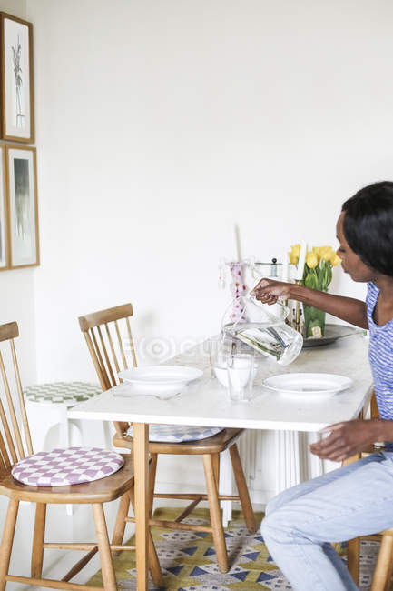 Side view of woman pouring water into glass from jug at dining table — Stock Photo