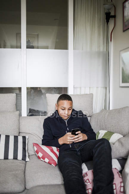 Teenage boy using smart phone on sofa at home - foto de stock