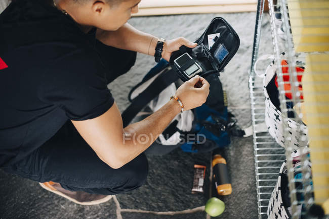 Blick aus der Vogelperspektive: Mann bereitet Diabetes-Kit vor, während er zu Hause hockt — Stockfoto