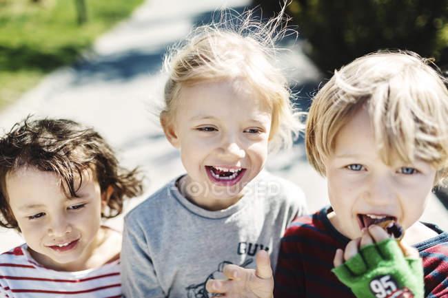 Портрет щасливий хлопчик їсть морозиво під час прогулянки з друзями на дворі — стокове фото
