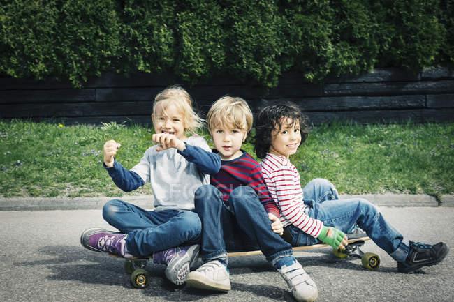 Retrato dos amigos felizes que sentam-se no skate de encontro às árvores — Fotografia de Stock
