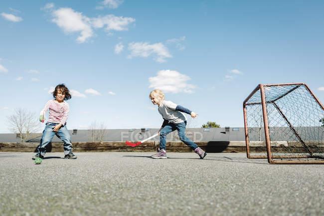 Enfants jouant au hockey à la cour contre le ciel bleu — Photo de stock