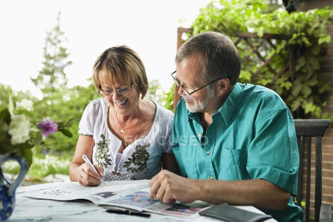 Casal sênior feliz resolvendo palavras cruzadas no jornal juntos — Fotografia de Stock