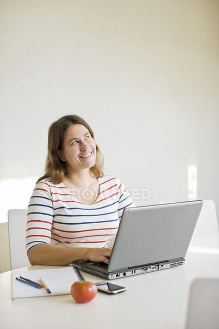 Femme adulte de milieu heureux regardant loin tout en utilisant l'ordinateur portatif — Photo de stock