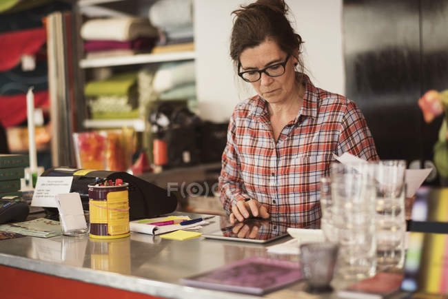 Owner using digital tablet at checkout counter in store — Stock Photo