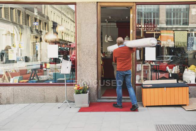 Opinião traseira o transporte do proprietário rolou acima do tapete ao andar para a loja — Fotografia de Stock