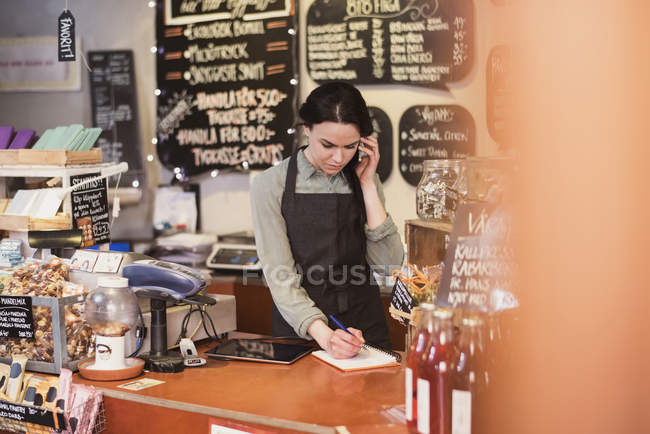 Owner talking on phone while writing on note pad at checkout counter in store — Stock Photo