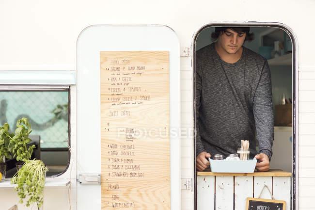 Männlicher Besitzer stellt Container an Foodtruck-Fenster — Stockfoto