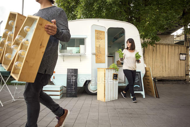 Besitzer tragen Buchstabe m und Topfpflanzen bei Spaziergang vor Food-Truck auf Straße — Stockfoto