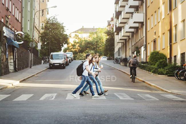 Vista lateral de adolescentes cruzando a estrada em cidade — Fotografia de Stock