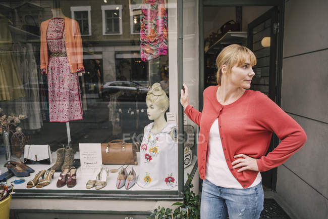 Confident owner standing against store looking away with hand on hip — Stockfoto