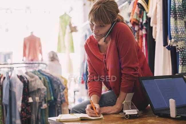 Жінка письмово порядку в щоденнику під час розмови на смарт-телефон ощадливість магазин — стокове фото