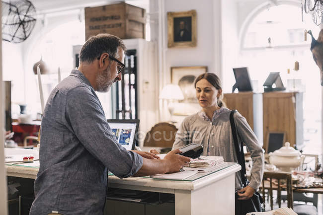 Owner using card reader in front of female customer at shop counter — Stock Photo