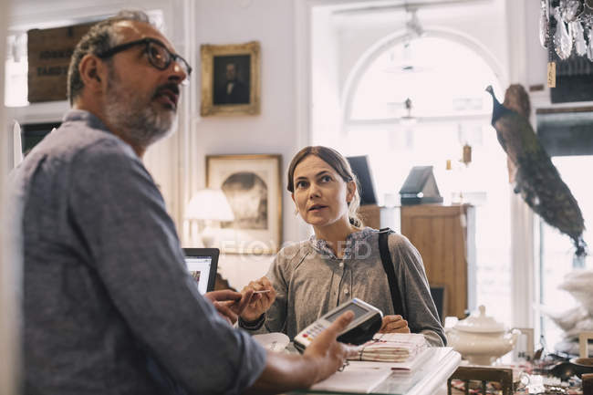 Proprietario con cliente femminile al banco del negozio — Foto stock