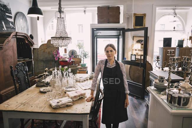 Ritratto di proprietaria femminile sicura in piedi in negozio di antiquariato — Foto stock