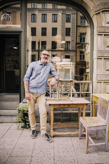 Sorrindo proprietário inclinado na cadeira fora loja de antiguidades — Fotografia de Stock